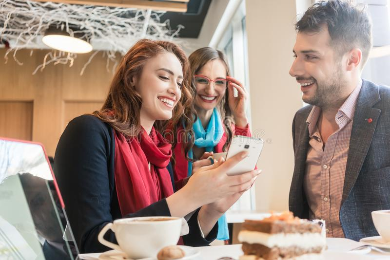 Three young friends using a mobile phone for fun during a coffee break royalty free stock photography
