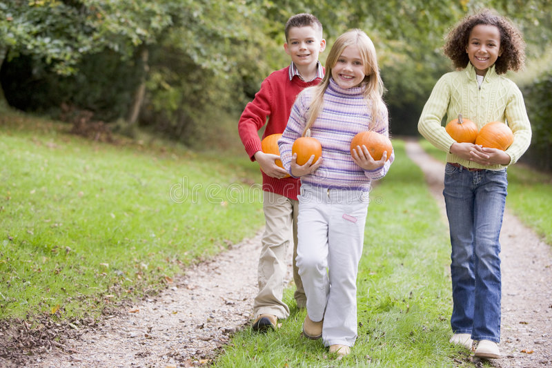 Download Three Young Friends Walking On Path With Pumpkins Stock Photo - Image: 5942488