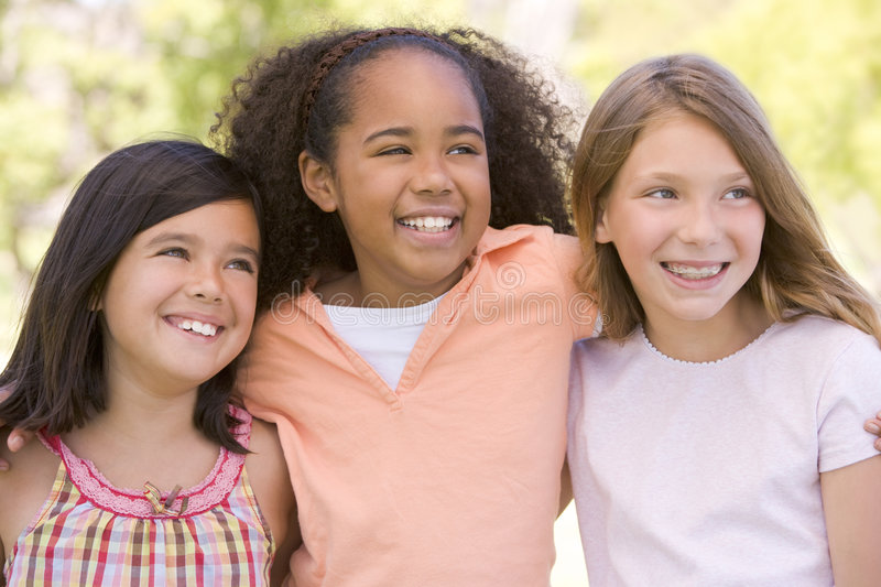 Three young girl friends outdoors smiling stock image