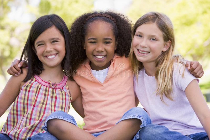 Three young girl friends sitting outdoors royalty free stock image