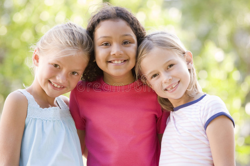 Three young girl friends standing outdoors smiling stock image
