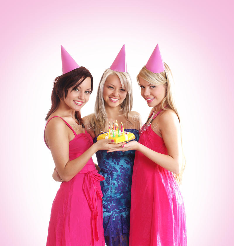 Three young girls are celebrate a birthday party. Three young and beautiful girls are celebrate a birthday party with a cake. The image is isolated on a light royalty free stock image