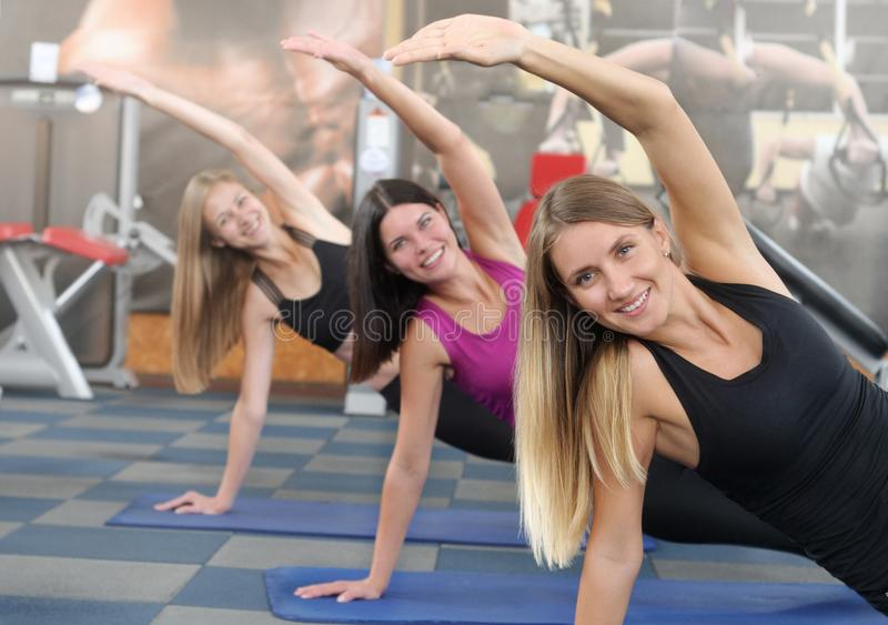 Three young girls doing a plank on exercise mat at gym stock images