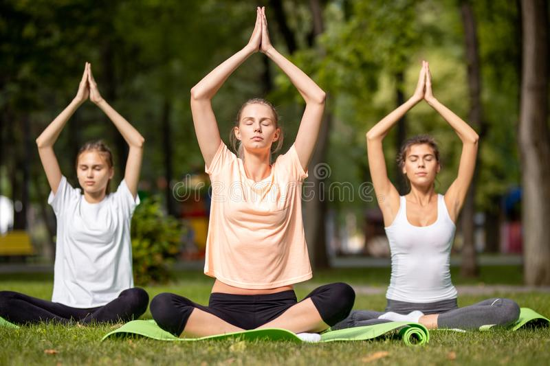 Three young girls doing yoga sitting on yoga mats on green grass in the park on a warm day royalty free stock photo