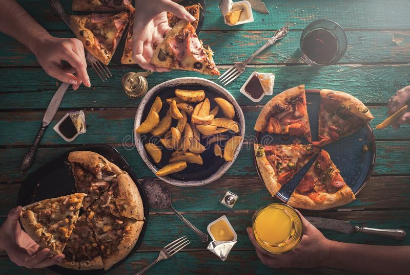 Three young girls eat pizza and drink carbonated drinks. View fr. Om above. Friendly Party royalty free stock images