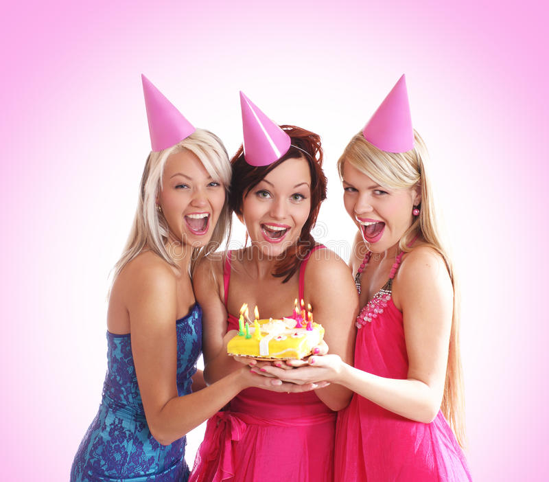 Three young girls are having a birthday party. Three young and beautiful girls in pretty dresses are celebrating a birthday party. The image is taken on a ligh stock image