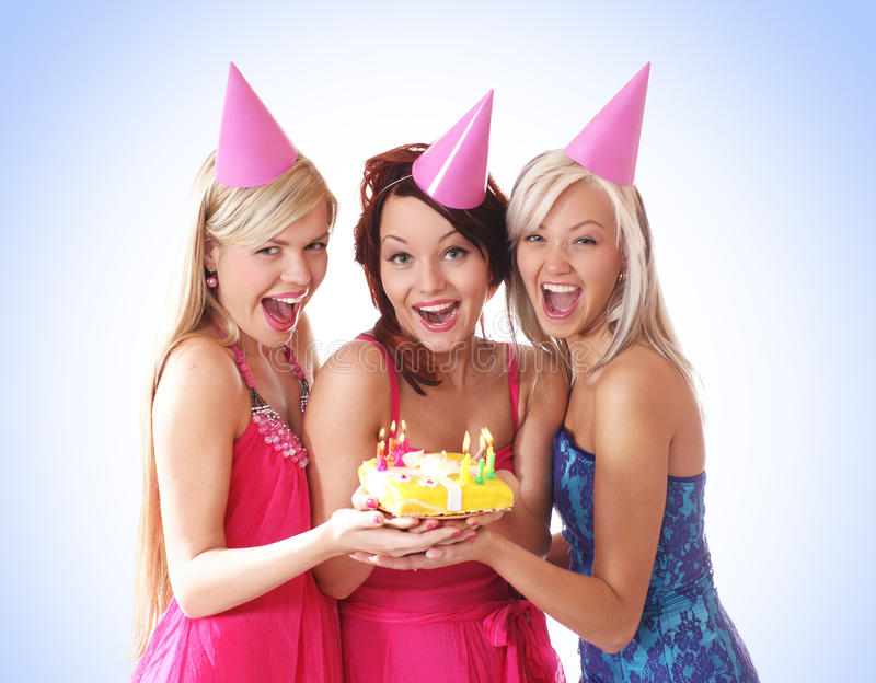 Three young girls are having a birthday party. Three young beautiful girls are celebrating a birthday party. The image is taken on a light blue gradient royalty free stock images