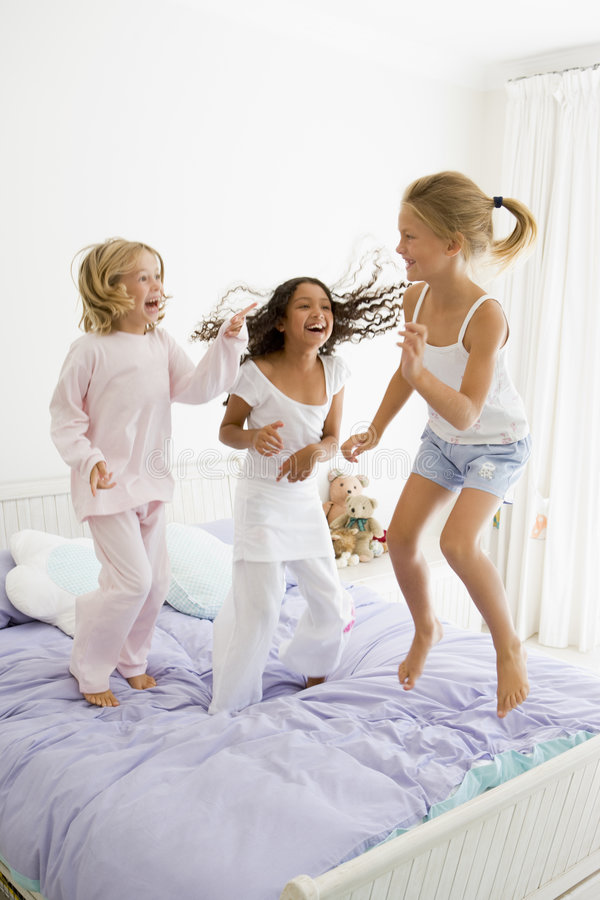 Three Young Girls Jumping On A Bed stock image