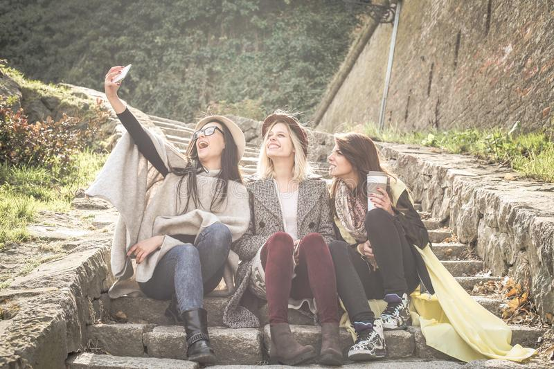 Three young girls sitting on the stairs at the public park. Three best friend making self picture in the public park. Girls. Sitting on stairs stock image