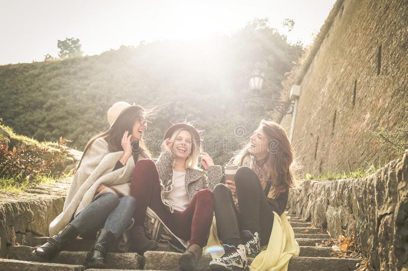 Three young girls sitting on the stairs at the public park. Three young girls sitting on the stairs at the public park an having royalty free stock image