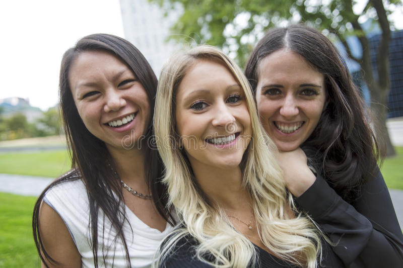 Three young good girl friend people in the city stock photos