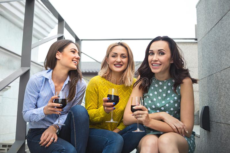 Three young happy woman laughing, drinking red wine, having fun stock photos
