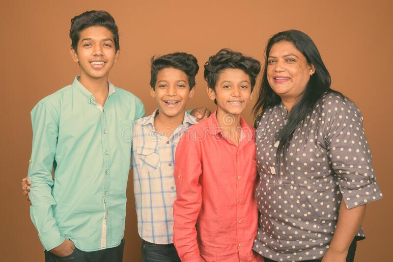 Three young Indian brothers and their mother together against brown background. Studio shot of three young Indian brothers and their mother together against stock images