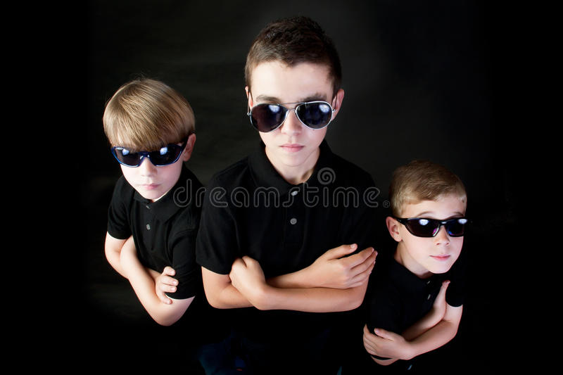 Three Young Men in Black. Three brothers with attitude dressed as FBI detectives stock images