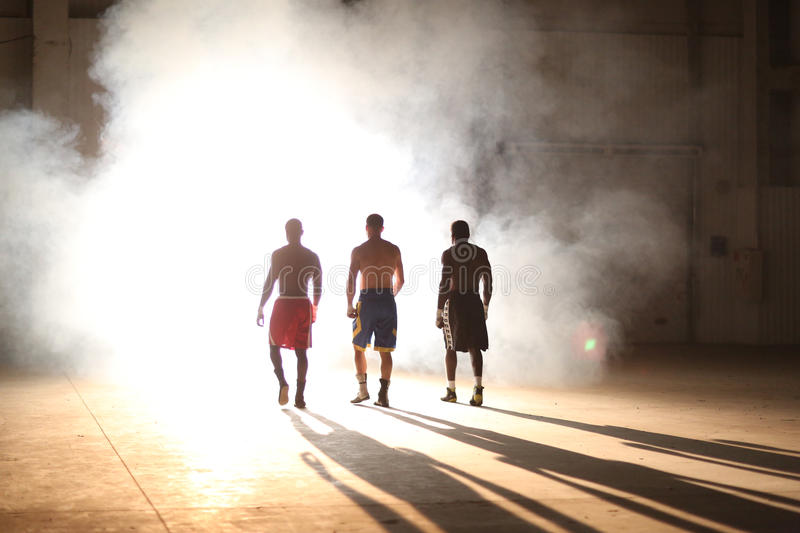 Three young men boxing workout in an old building stock image