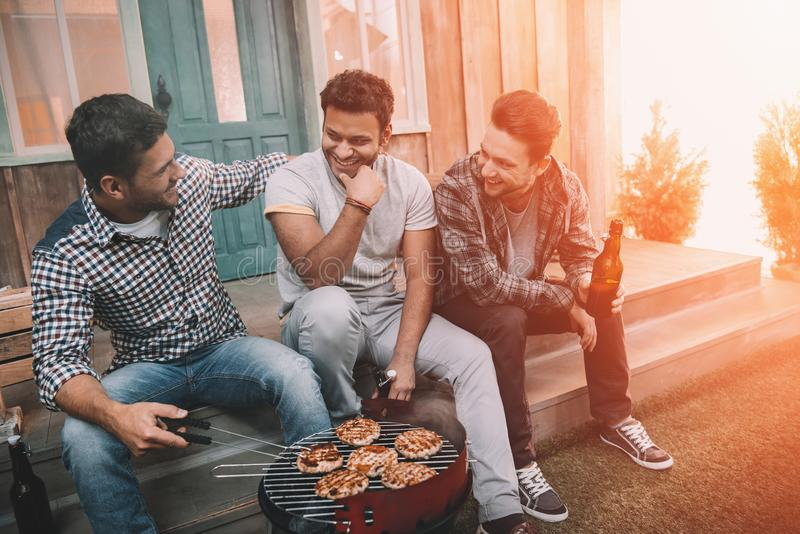 Three young men drinking beer and smiling while sitting on porch royalty free stock photo