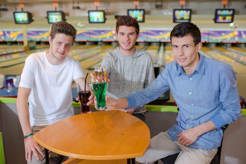 Three young men having drink stock photos