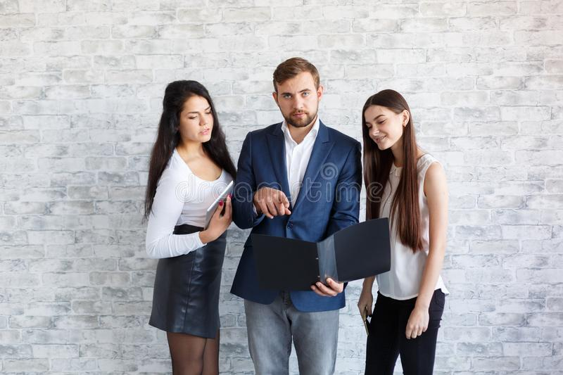 A guys and two girls, look at the documents in a folder. stock photography