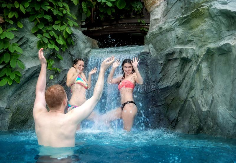 Three young people having fun with the falling water of the waterfall in the pool stock image