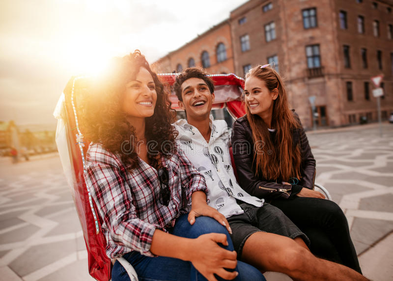 Three young people having fun on tricycle in the city stock photo