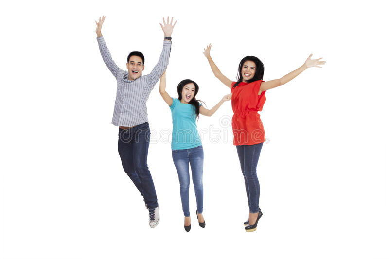 Three young people jumping in studio stock photography