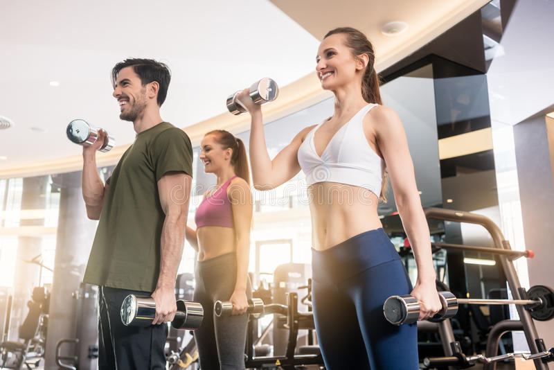 Three young people smiling while alternating dumbbell bicep curl. Low-angle view of three young people smiling while alternating dumbbell bicep curl exercise royalty free stock images