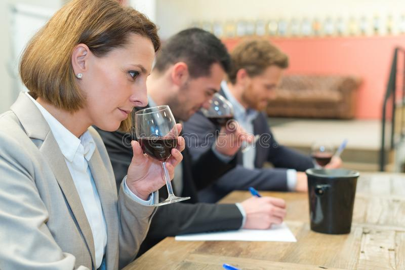 Three young people taking notes while doing wine tasting stock photography
