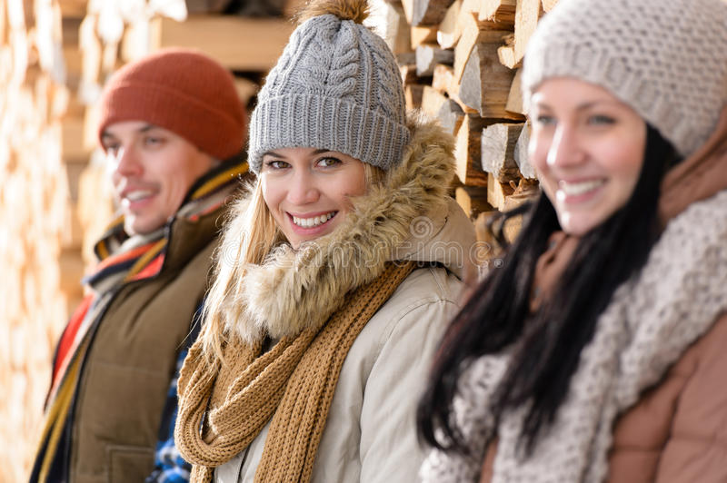 Three young people winter fashion wooden logs royalty free stock image