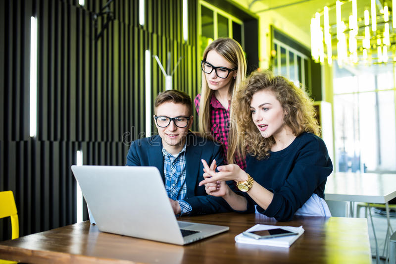 Three young people working together on a new project. Team of happy office people working on laptop computer, smiling. stock image