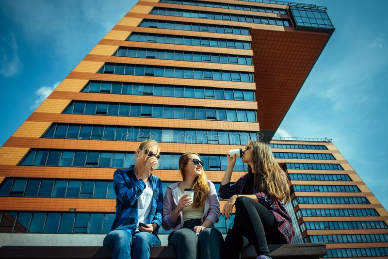 Three young pretty girlfriends sitting on bench on city street and talking. Women drink coffee from disposable glasses royalty free stock image