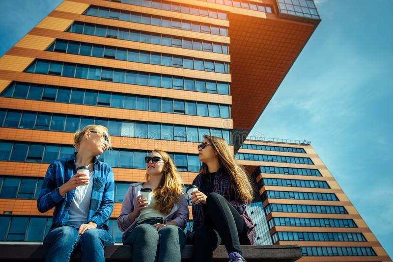 Three young pretty women sit on a bench on a city street, drinking coffee from disposable glasses, talking and laughing. Friendly stock images