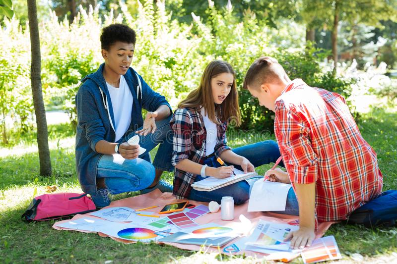 Three young progressive designers working in nature. In nature. Three young progressive designers feeling joyful and creative while working in nature royalty free stock images