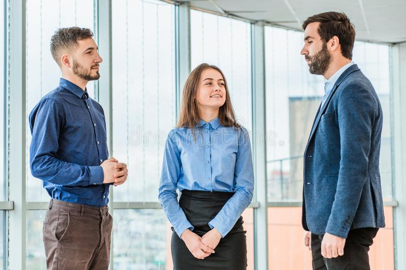 Three young, serious partners are in the office and talk to each other. By this time, they are all dressed in business stock photo