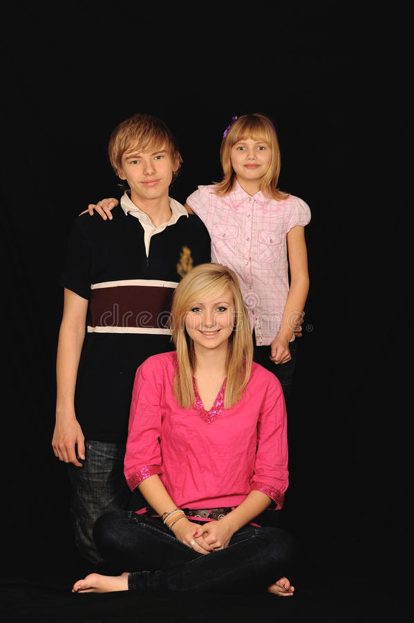 Three young siblings. Portrait isolated against a black background royalty free stock photography