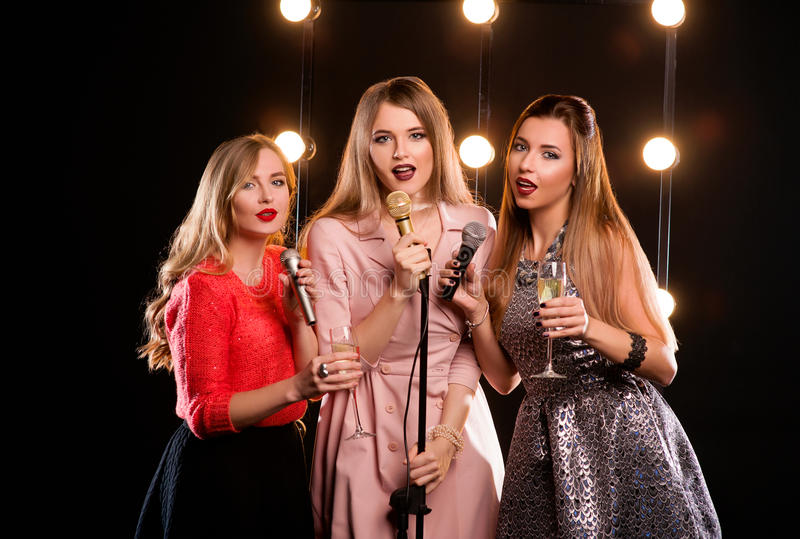 Three young smiley beautiful women in karaoke royalty free stock images