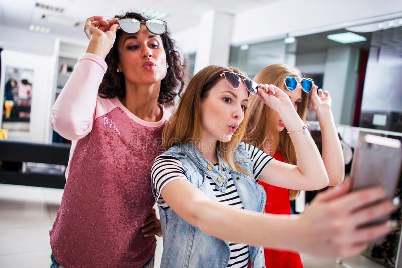 Three young stylish girlfriends raising fashionable sunglasses while taking selfie with smartphone in shopping mall.  stock images