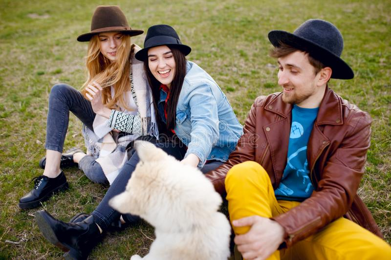 A three young stylish people spend time together outdoors with their husky dog sitting on green grass. royalty free stock photos