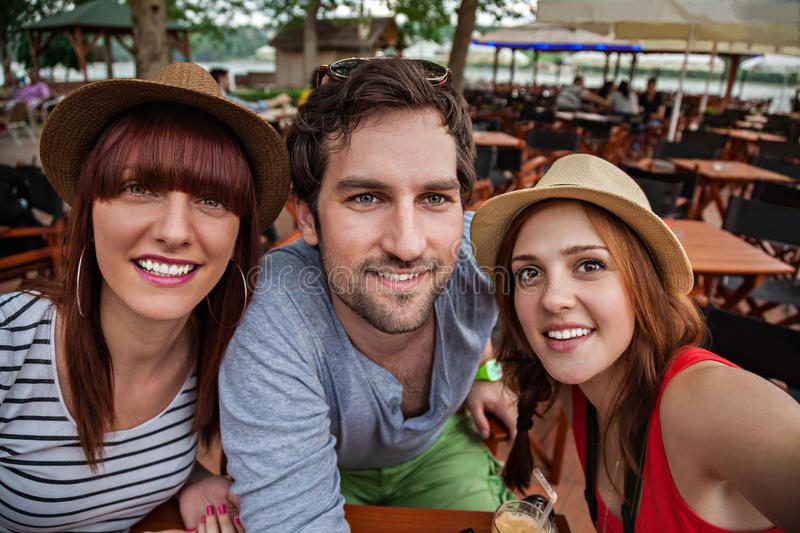 Three Young Taking Selfie. Three Young People In Cafe Taking Selfie royalty free stock photos
