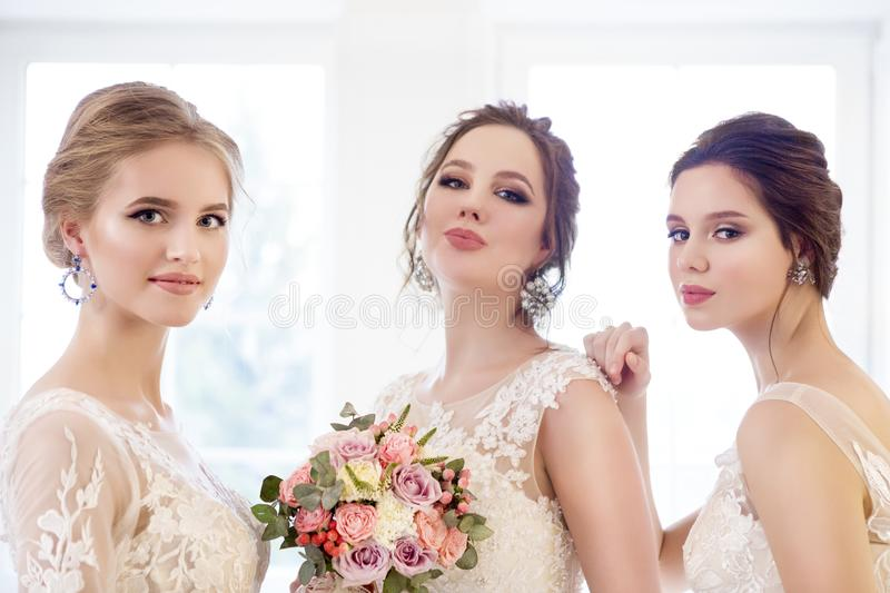 Young woman with bouquets wearing wedding dresses royalty free stock photos