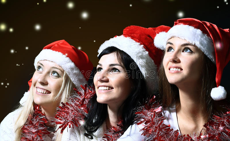 Three young women in costume of Santa Claus with shopping at the Christmas background royalty free stock photos