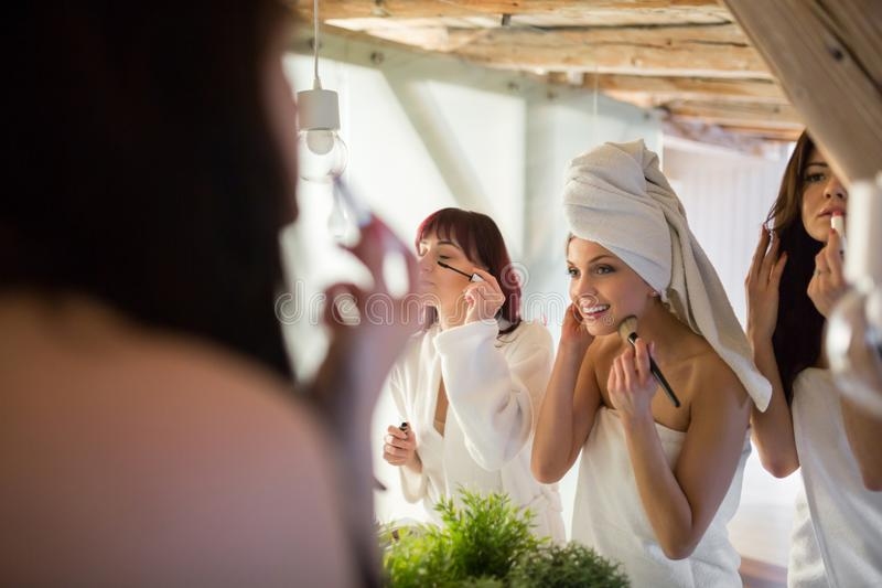 Three young women doing make up in bathroom royalty free stock photography