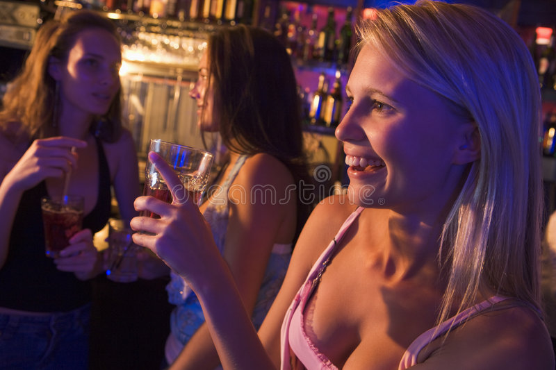 Three young women drinking at a nightclub stock photography