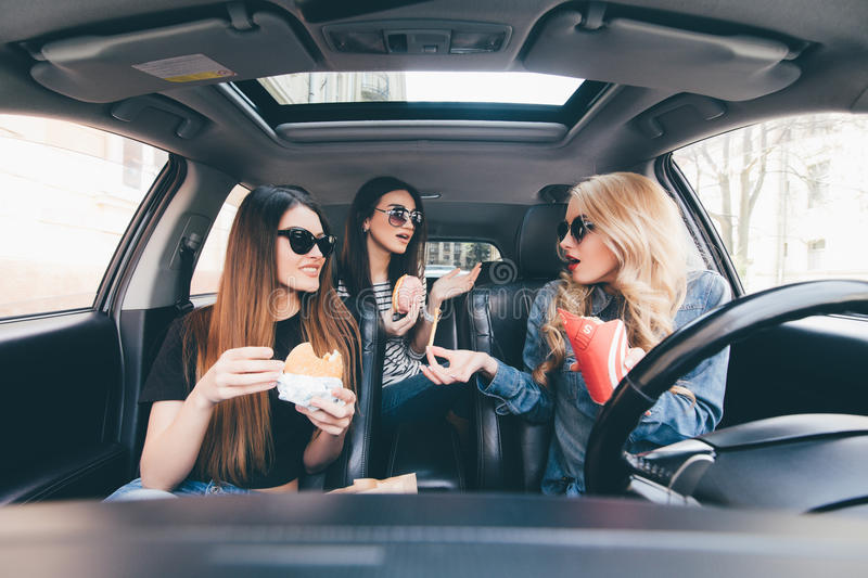 Three young women drive a car, speaking each other and eating a fast food in a car in traffic jam. Three young women drive a car, speaking each other and eating royalty free stock images