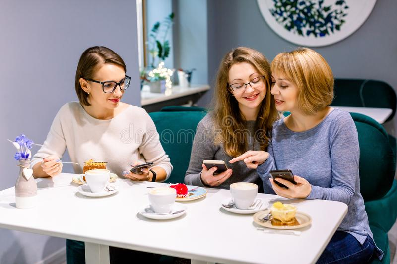 Three young women eating cakes and drinking coffee or tea at cafe, coffee break. Pretty girls sitting at cafe and using. Smartphones, making photos stock photo