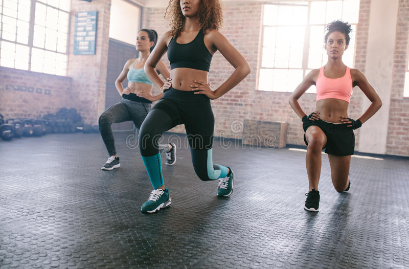 Three young women exercising in gym royalty free stock image