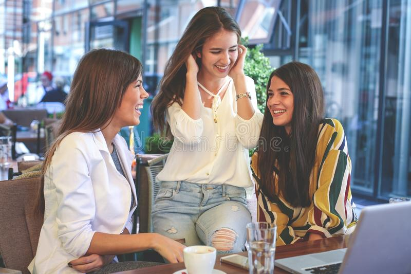 Three young women having conversation in cafe. Girls having break coffee. royalty free stock photography
