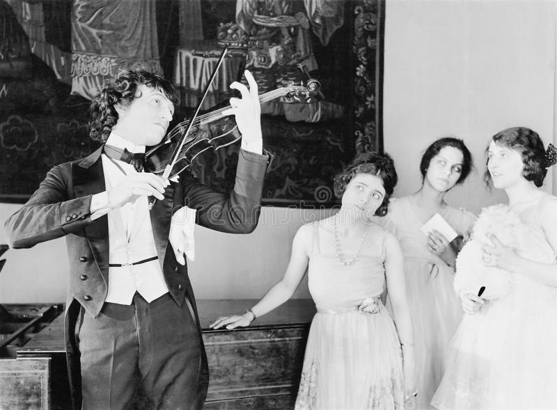 Three young women looking with adoration at a violin player. (All persons depicted are no longer living and no estate exists. Supplier grants that there will be stock photo