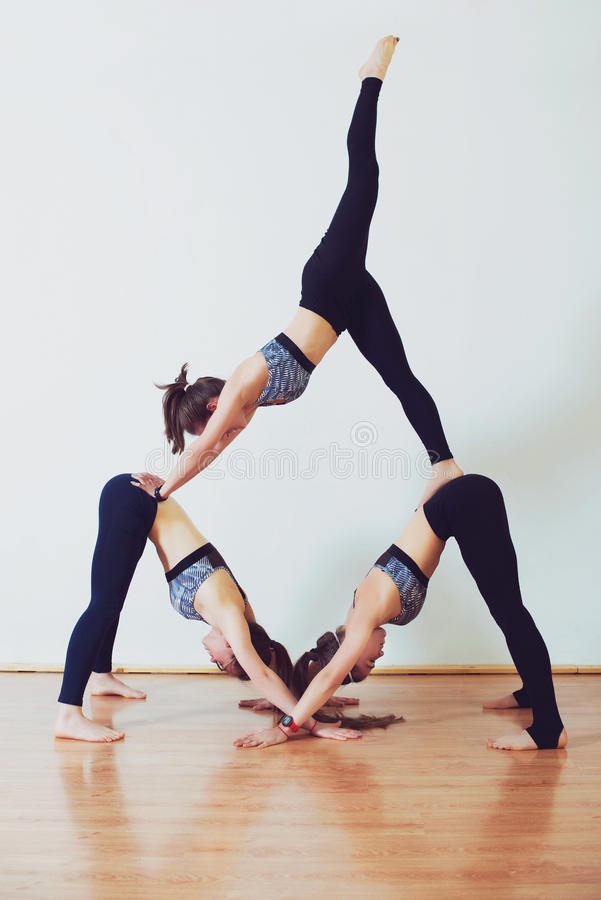Three young women practicing acro yoga in white studio. royalty free stock images