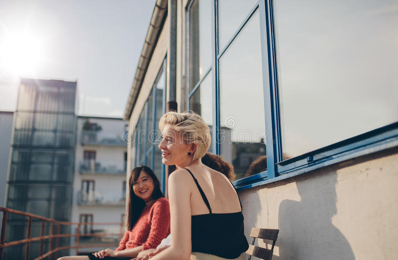 Three young women sitting in balcony. On a sunny day. Female friends enjoying free time together outdoors stock image
