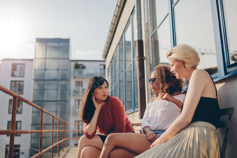Three young women sitting outdoors and chatting. Multiracial group of females relaxing in terrace royalty free stock photography